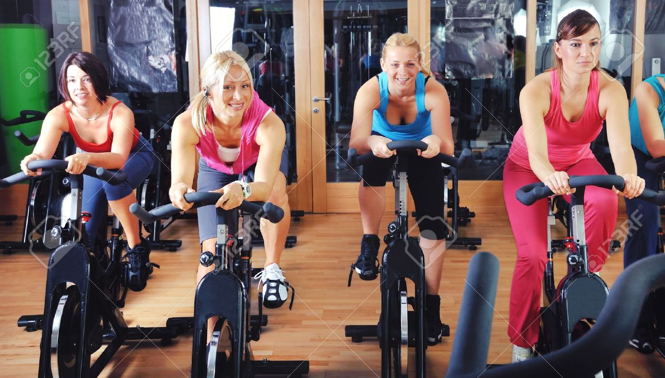 21511368-Beautiful-women-doing-exercise-in-a-spinning-class-at-gym-Stock-Photo