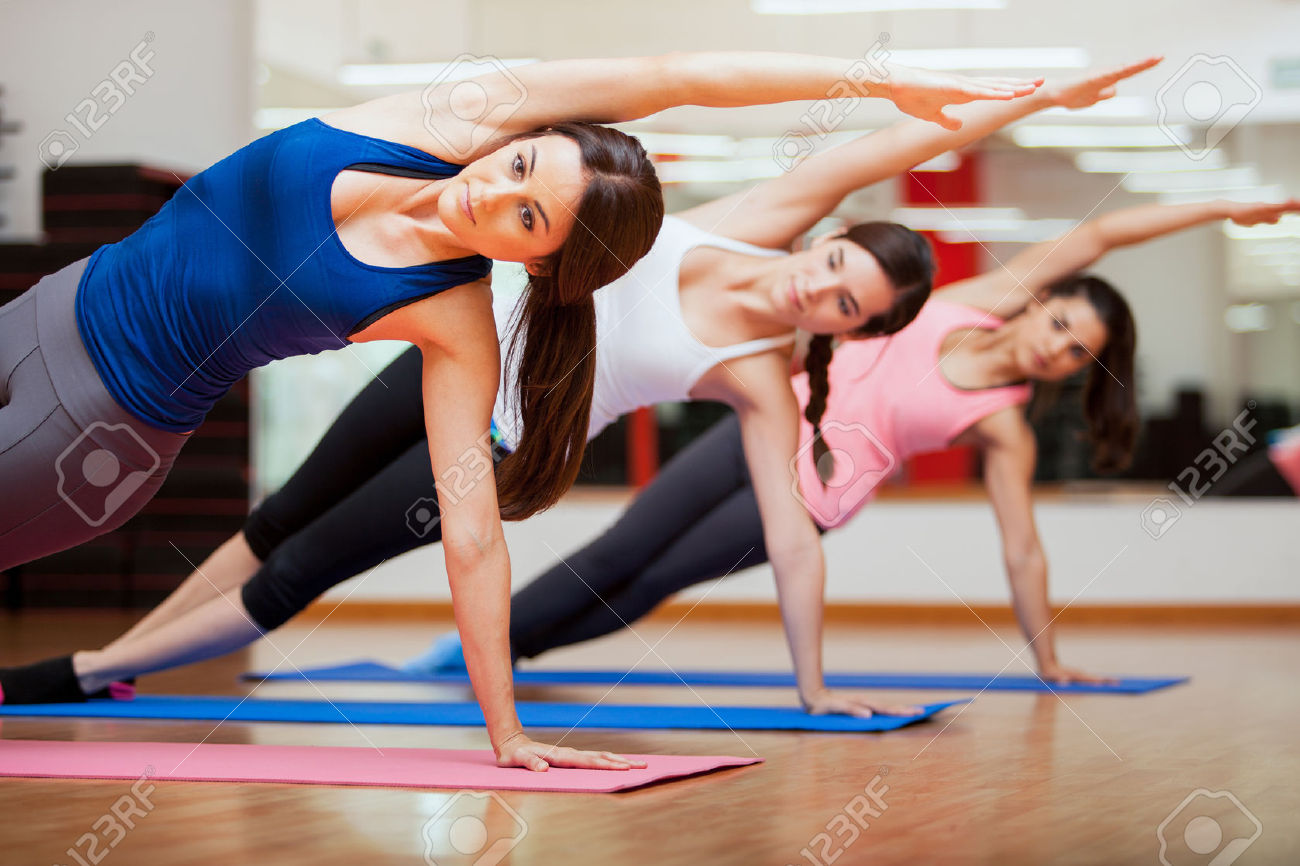24382136-Beautiful-group-of-women-practicing-the-side-plank-yoga-pose-during-a-class-in-a-gym-Stock-Photo